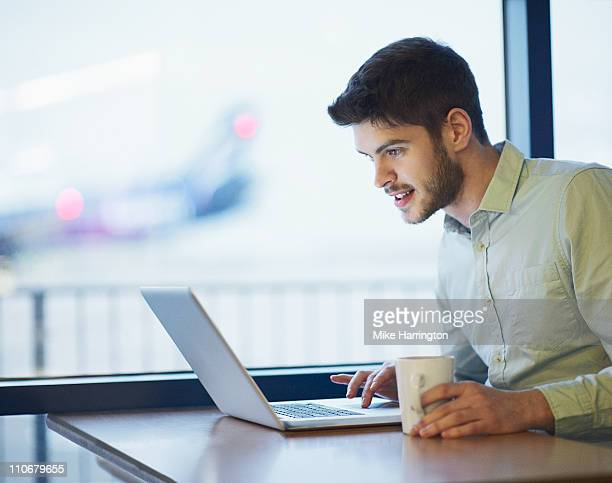 Young Man Using Laptop In Airport Cafe