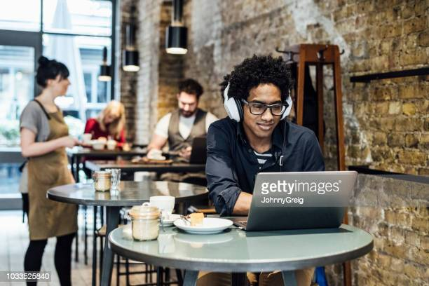 young man using laptop in cafe and listening to music - remote work stock pictures, royalty-free photos & images