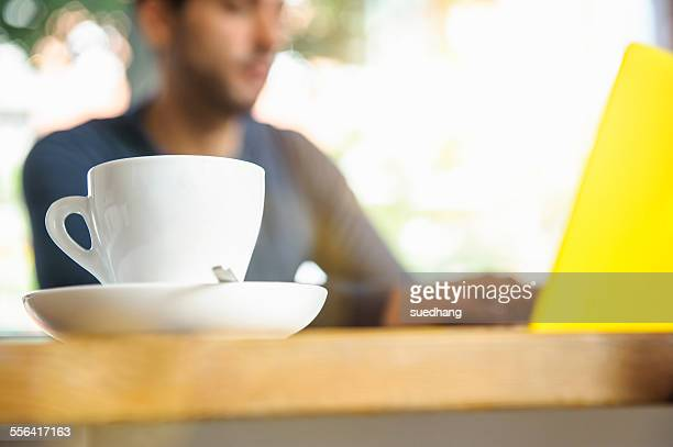 Young man using laptop in cafe, low angle view