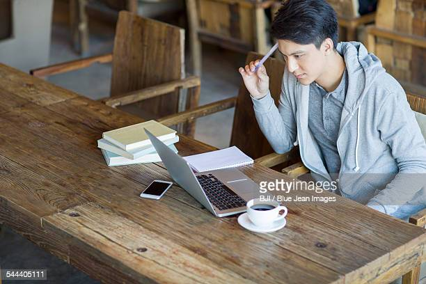 Young man using laptop in cafe