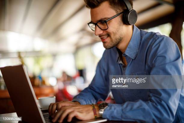 young man using laptop in cafeteria - remote location stock pictures, royalty-free photos & images