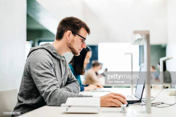 young man using laptop in library -  eラーニング ストックフォトと画像