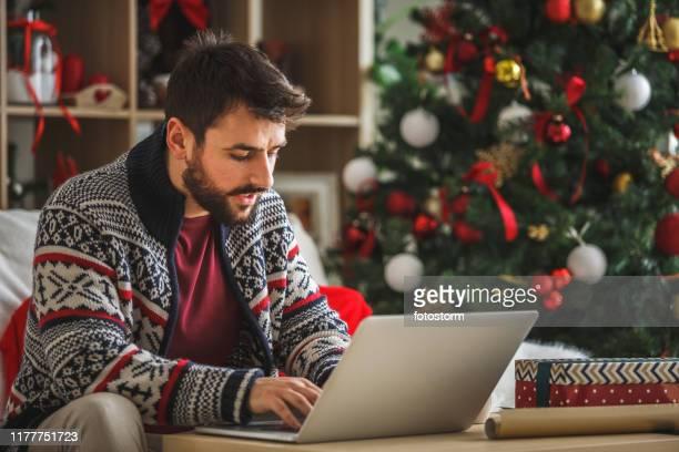 junger mann mit laptop im wohnzimmer in der nähe des weihnachtsbaumes - dezember stock-fotos und bilder