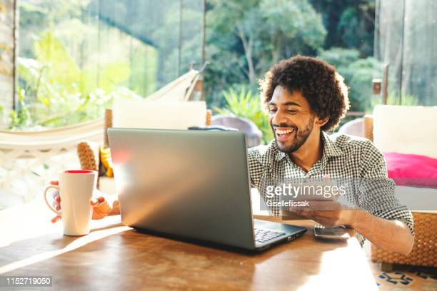 young man using laptop in the living room - telecommuting stock pictures, royalty-free photos & images