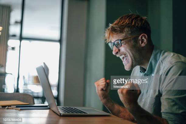young man using laptop, laughing happly - vreugde stockfoto's en -beelden