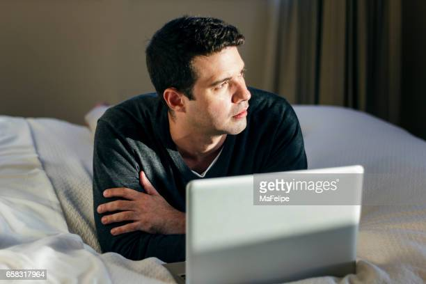 Young man using laptop lying in bed