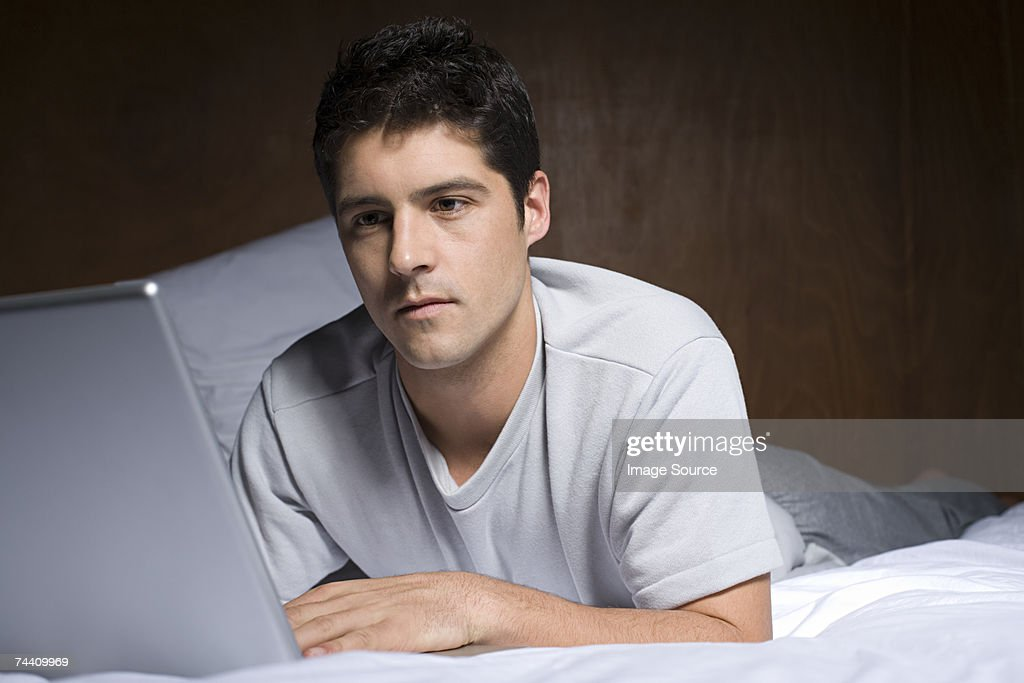 Young man using laptop on bed : Stock Photo