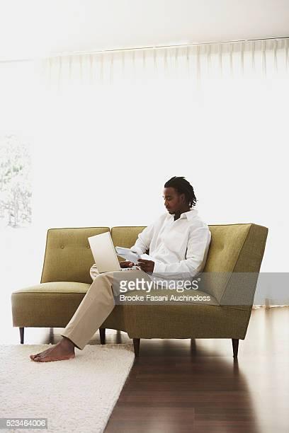 Young Man Using Laptop on Designer Sofa