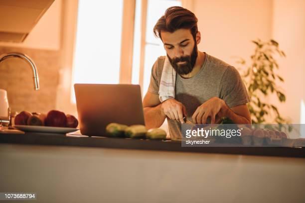 jovem usando laptop enquanto salada de corte para o almoço na cozinha. - só um homem - fotografias e filmes do acervo