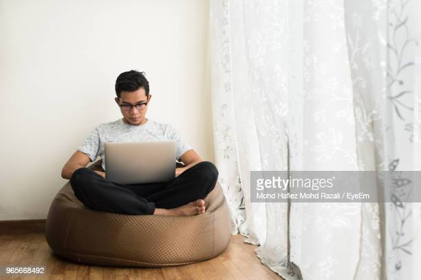 young man using laptop while sitting on bean bag by window at home - sacco photos et images de collection