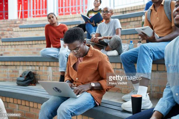 young man using laptop while sitting with friends - education stock pictures, royalty-free photos & images