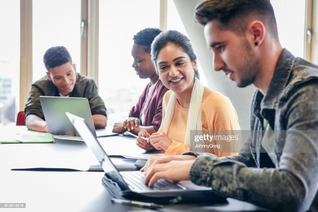 Young man using laptop with female student watching and smiling : Stock Photo