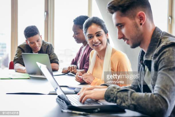 young man using laptop with female student watching and smiling - classroom stock pictures, royalty-free photos & images