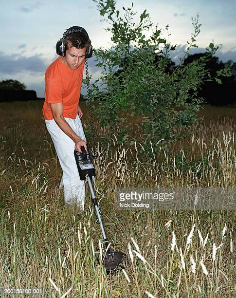 Young man using metal detector in field