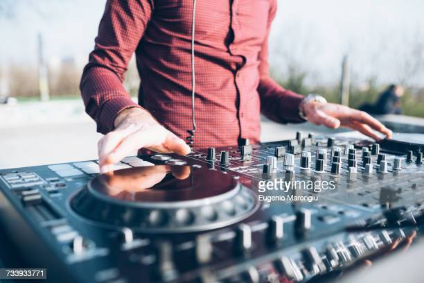 Young man using mixing desk at roof party, mid section, close-up