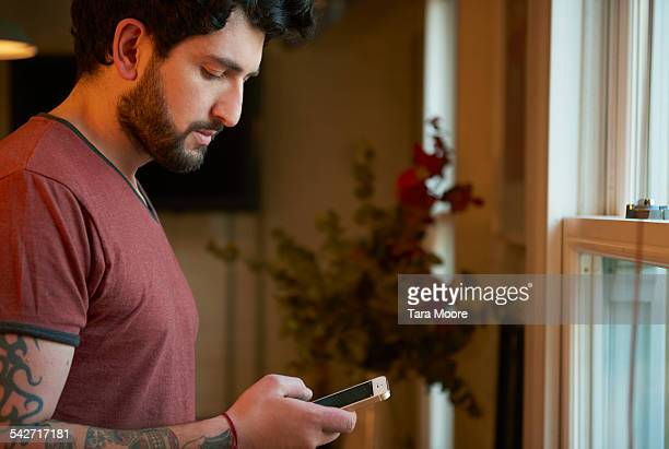Young man using mobile at home
