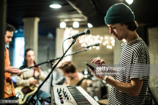 young man using mobile device at band rehearsal - singer stock pictures, royalty-free photos & images