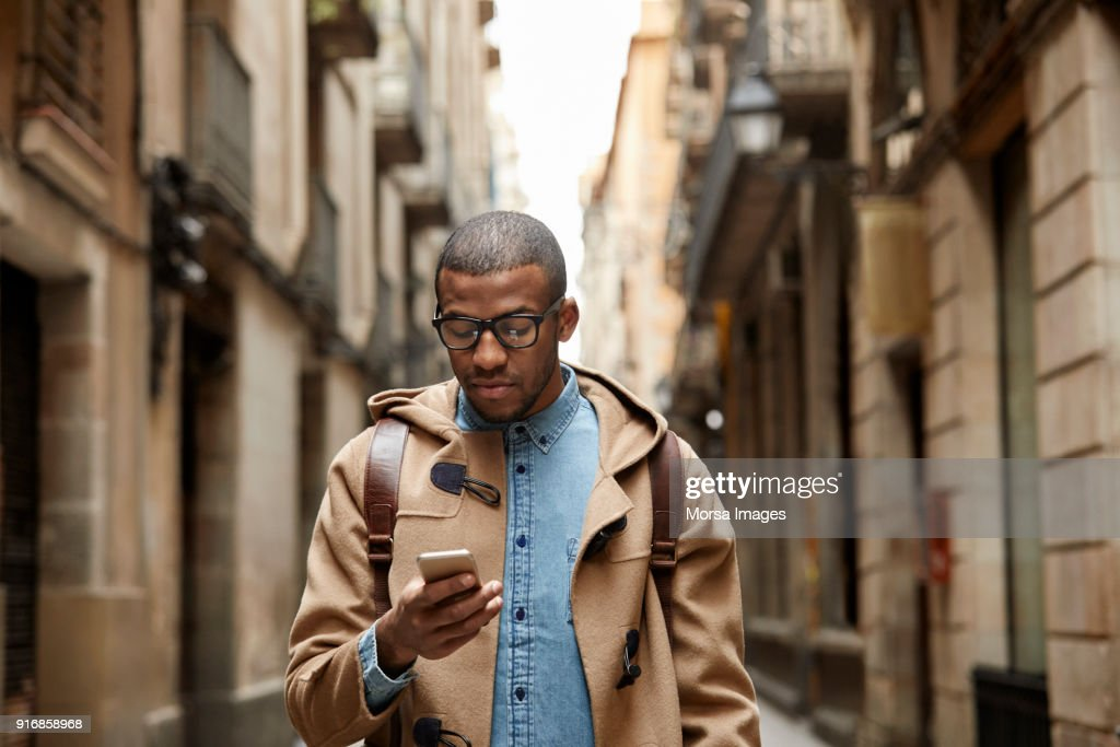 Young man using mobile phone amidst buildings : Stock Photo