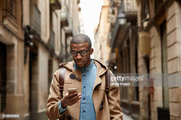 young man using mobile phone amidst buildings - black alley stock photos and pictures