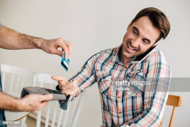 Young man using mobile phone and giving his credit card to the waiter at the coffee shop