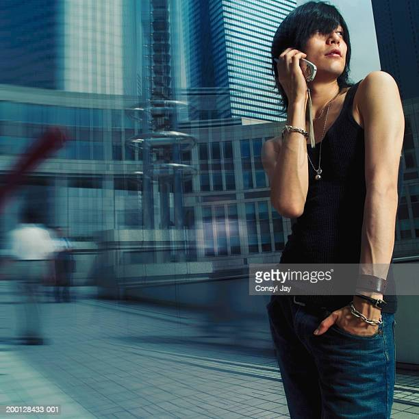 Young man using mobile phone by office buildings (Digital Composite)