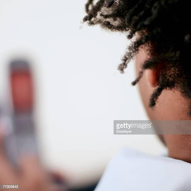 Young man using mobile phone, close up, rear view