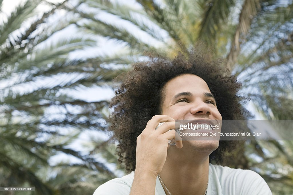 Young man using mobile phone in front of palm trees, low angle view : Stock Photo