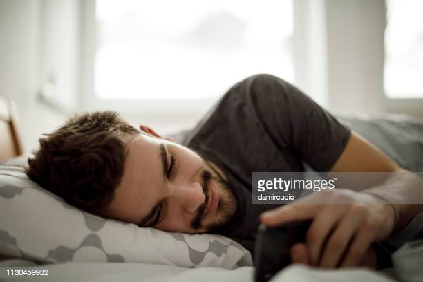young man using mobile phone in the bed - mood stream stock pictures, royalty-free photos & images