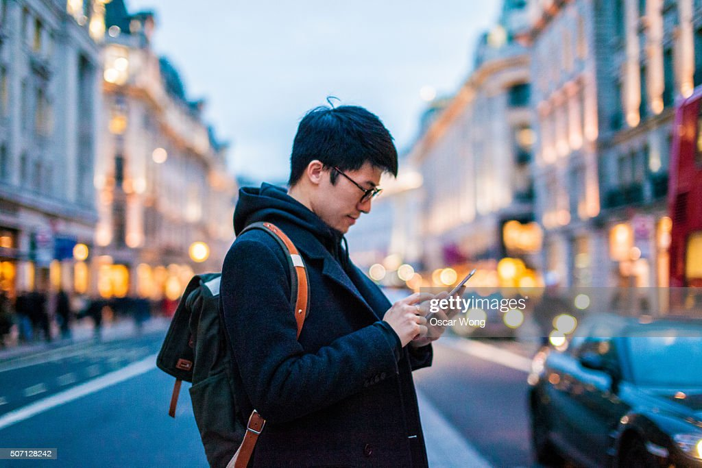 Young man using mobile phone on the street : Stock-Foto