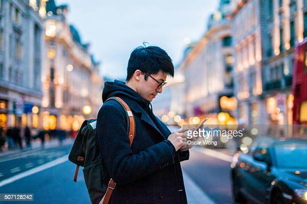 young man using mobile phone on the street - man city stock photos and pictures