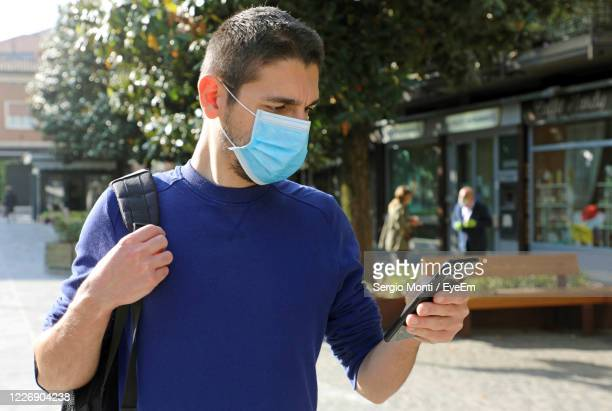 young man using mobile phone - 追跡 ストックフォトと画像