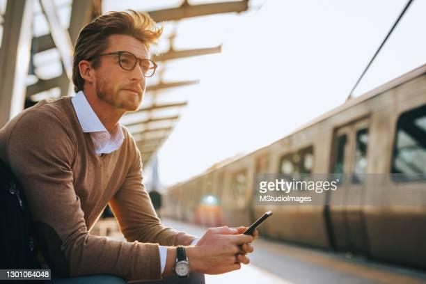 junger mann mit handy - bahnreisender stock-fotos und bilder