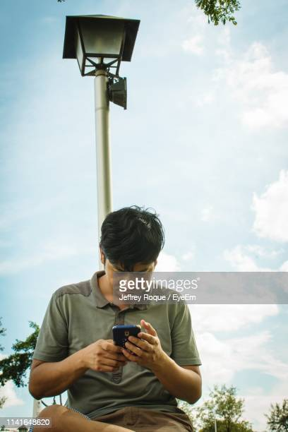 young man using mobile phone while sitting by street light against sky - jeffrey roque stock photos and pictures