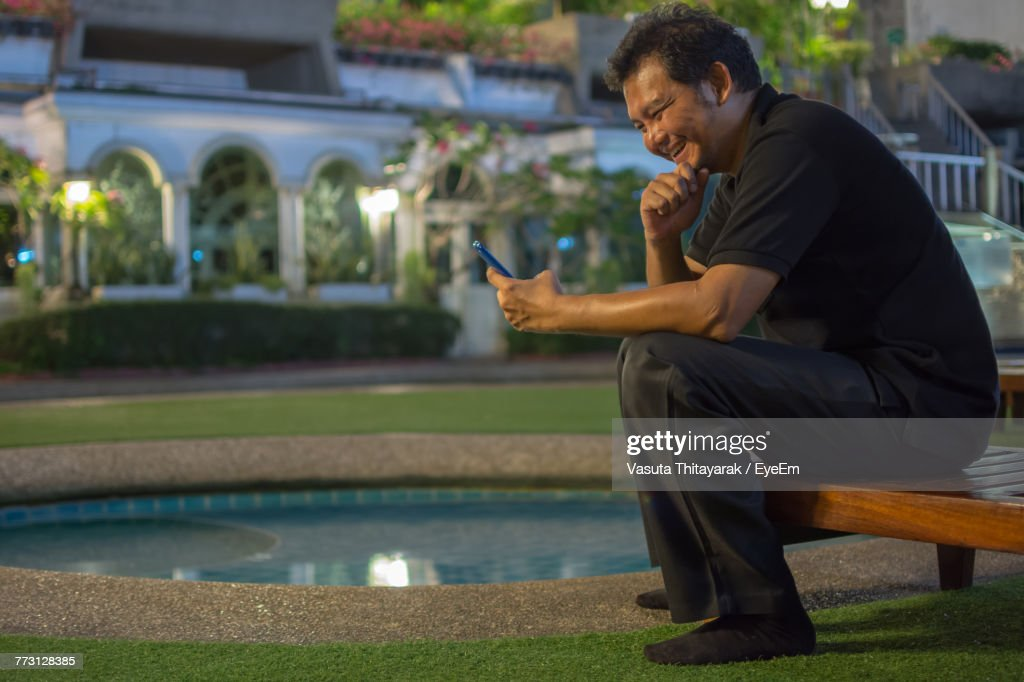 Young Man Using Mobile Phone While Sitting On Lounge Chair : Photo