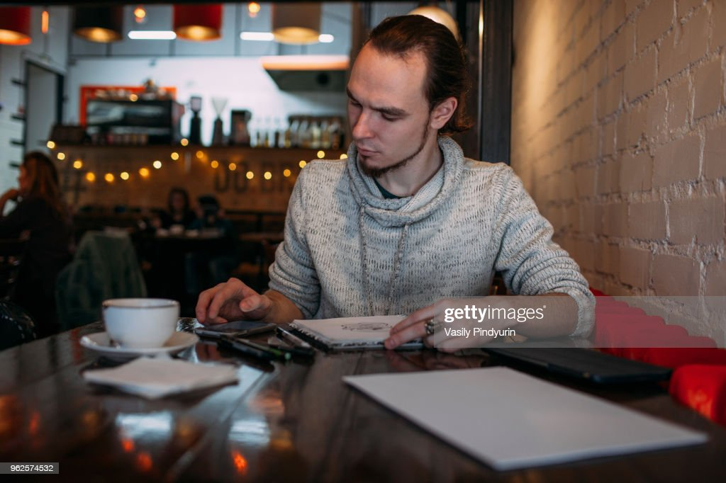 Young man using mobile phone while sitting with book on table at cafe : Stock Photo