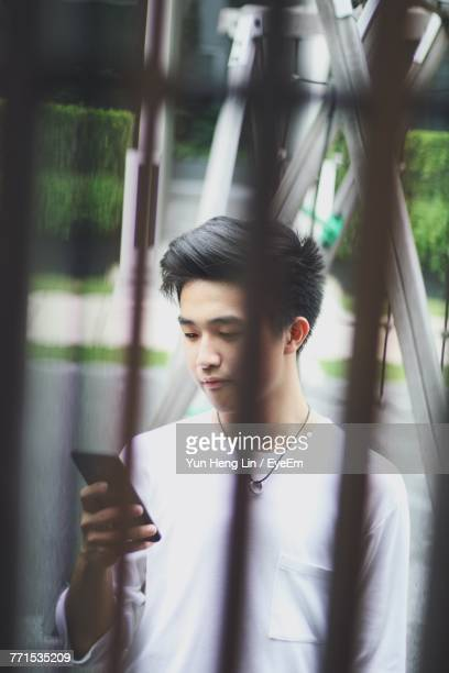 Young Man Using Mobile Phone While Standing On Street Seen Through Fence