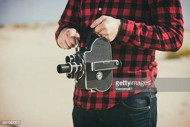 Young man using old film camera on the beach, close-up