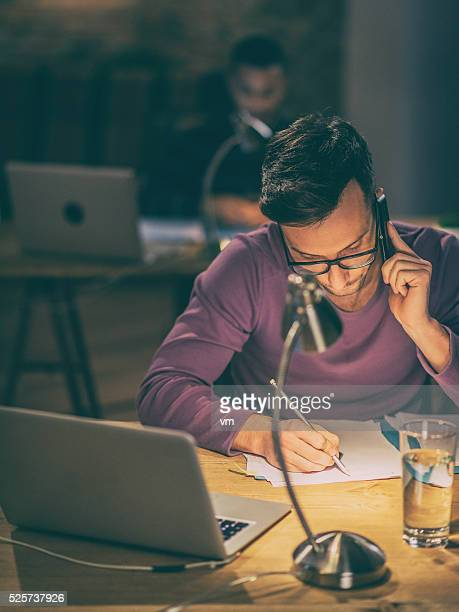 Young man using phone and writing on paper