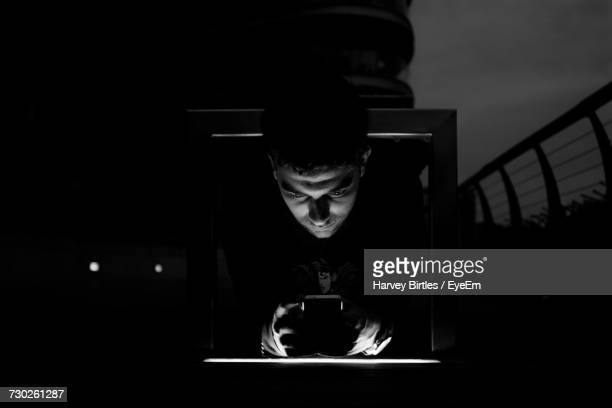 Young Man Using Phone By Railing At Night