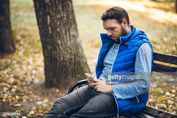 young man using phone in a park - phone message stock pictures, royalty-free photos & images