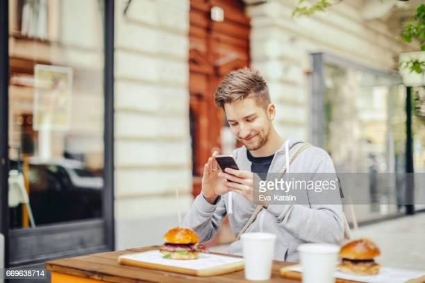 Ung man med telefonen i restaurangen