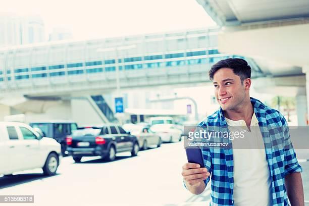 Young man using phone on Dubai station