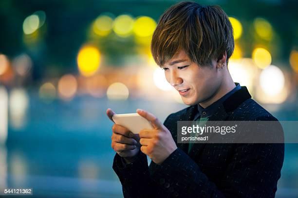 若い男性電話を使用して通りを夜に