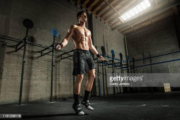 young man using skipping rope in gym - sin camisa fotografías e imágenes de stock