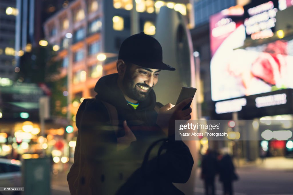 Young man using smart device to navigate through city. : Stock Photo