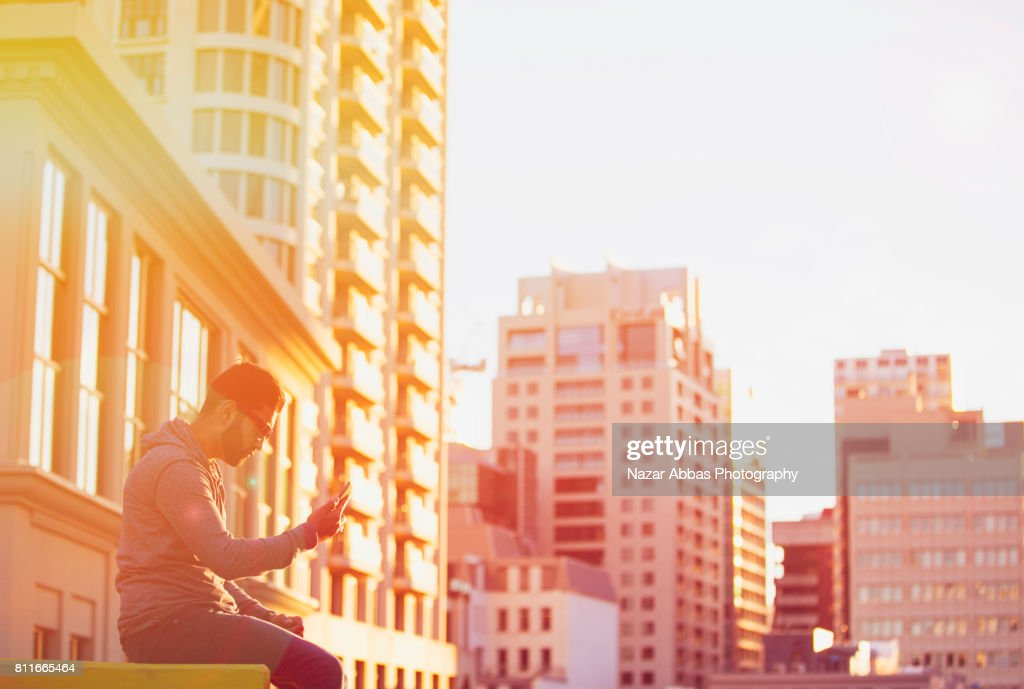 Young Man Using Smart Device With Background Of Building. : Stock Photo