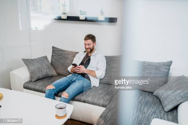 young man using smart phone and listening to music on the sofa - slovenia foto e immagini stock