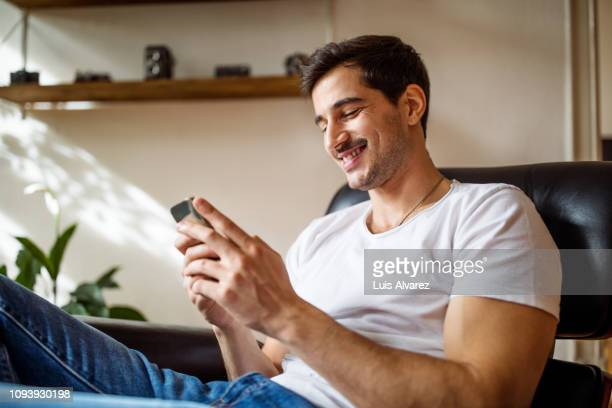 young man using smart phone at home - ソファ ストックフォトと画像