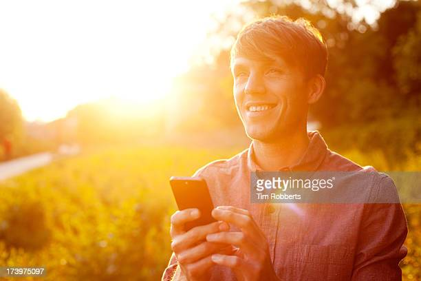 Young man using smart phone at sunset.