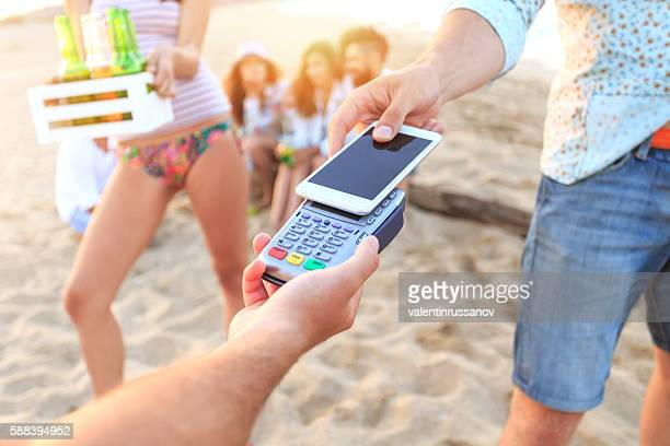 Young man using smart phone for contactless payment on beach